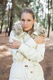 Cute woman shivering while having a walk in a forest