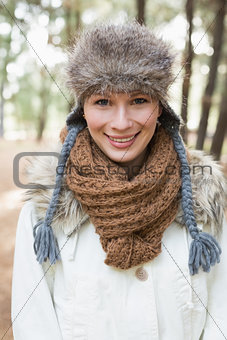 Beautiful woman wearing fur hat with woolen scarf and jacket in woods