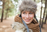 Woman in fur hat with woolen scarf in the woods