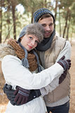 Couple in winter clothing embracing in the woods