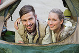 Smiling couple lying in tent after a hike