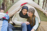 Smiling couple in tent with backpack in the wilderness