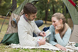 Young couple with a map lying in tent