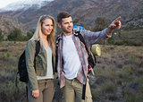 Couple with backpacks standing on landscape