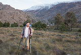 Man with backpack and trekking poles walking on landscape