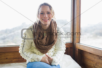 Cute woman sitting in warm clothing in cabin