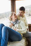 Loving couple in winter clothing sitting in cabin