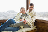 Couple in winter clothing sitting against cabin window