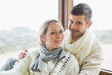 Couple in winter clothing against cabin window