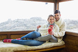 Couple in winter wear with coffee cups against cabin window
