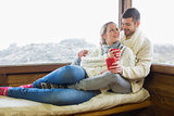 Loving couple in winter wear with cups against cabin window