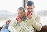 Couple in winter clothing drinking coffee against window