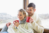 Couple in winter wear drinking coffee against window
