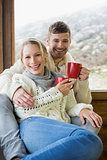 Cheerful couple in winter clothing holding cups against window