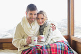 Loving couple in winter wear with cups against window