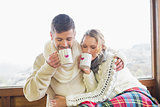 Loving couple in winter wear drinking coffee against window