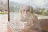 Content woman with coffee cup looking through window