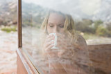 Woman drinking coffee through cabin window
