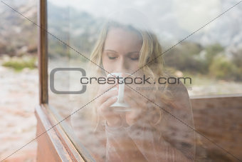 Woman drinking coffee through cabin window
