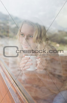 Thoughtful content woman with coffee cup looking out through window