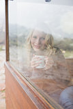 Content woman with coffee cup looking out through window