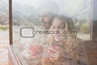 Thoughtful content couple with cups looking through window