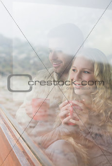 Thoughtful happy couple with coffee cups looking through window