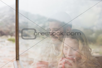 Thoughtful couple with coffee cups seen through cabin window