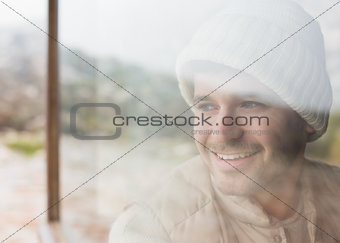 Thoughtful smiling man looking out through window