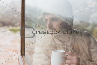 Thoughtful man with cup looking out through window
