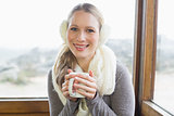 Smiling woman wearing earmuff with coffee cup sitting against window