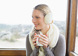 Smiling woman wearing earmuff with coffee cup against window