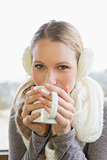 Woman wearing earmuff while drinking coffee
