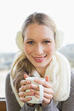 Smiling woman wearing earmuff with drinking coffee