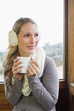 Smiling woman wearing earmuff with cup against window