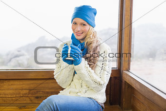 Cute woman with cup sitting in warm clothing against window