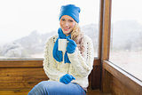 Woman with cup sitting in warm clothing against window