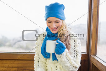 Woman with coffee cup in warm clothing against window