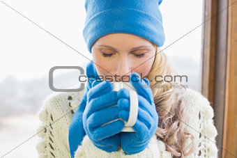 Cute woman drinking coffee in warm clothing