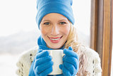 Smiling woman with cup in warm clothing against window