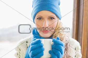 Cute woman with coffee cup in warm clothing