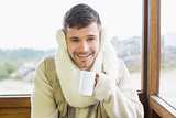 Smiling man wearing earmuff with coffee cup against window