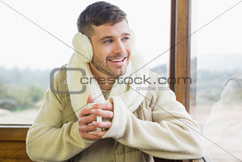 Man wearing earmuff with coffee cup against window