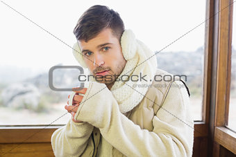 Man wearing earmuff while drinking coffee against window