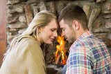 Romantic couple with eyes closed in front of fireplace