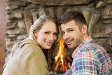 Smiling young couple in front of lit fireplace