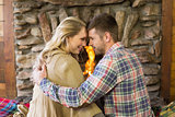 Loving couple looking at each other in front of lit fireplace