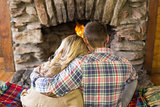 Romantic couple sitting in front of lit fireplace