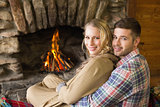Romantic young couple in front of lit fireplace