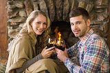 Romantic couple toasting wineglasses in front of lit fireplace